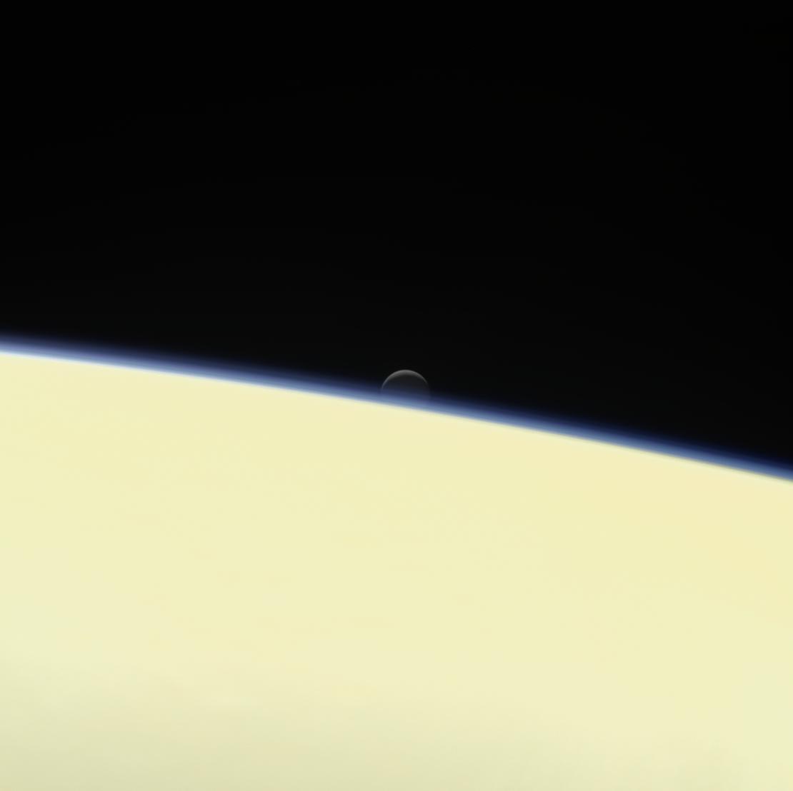 Enceladus sets behind Saturn