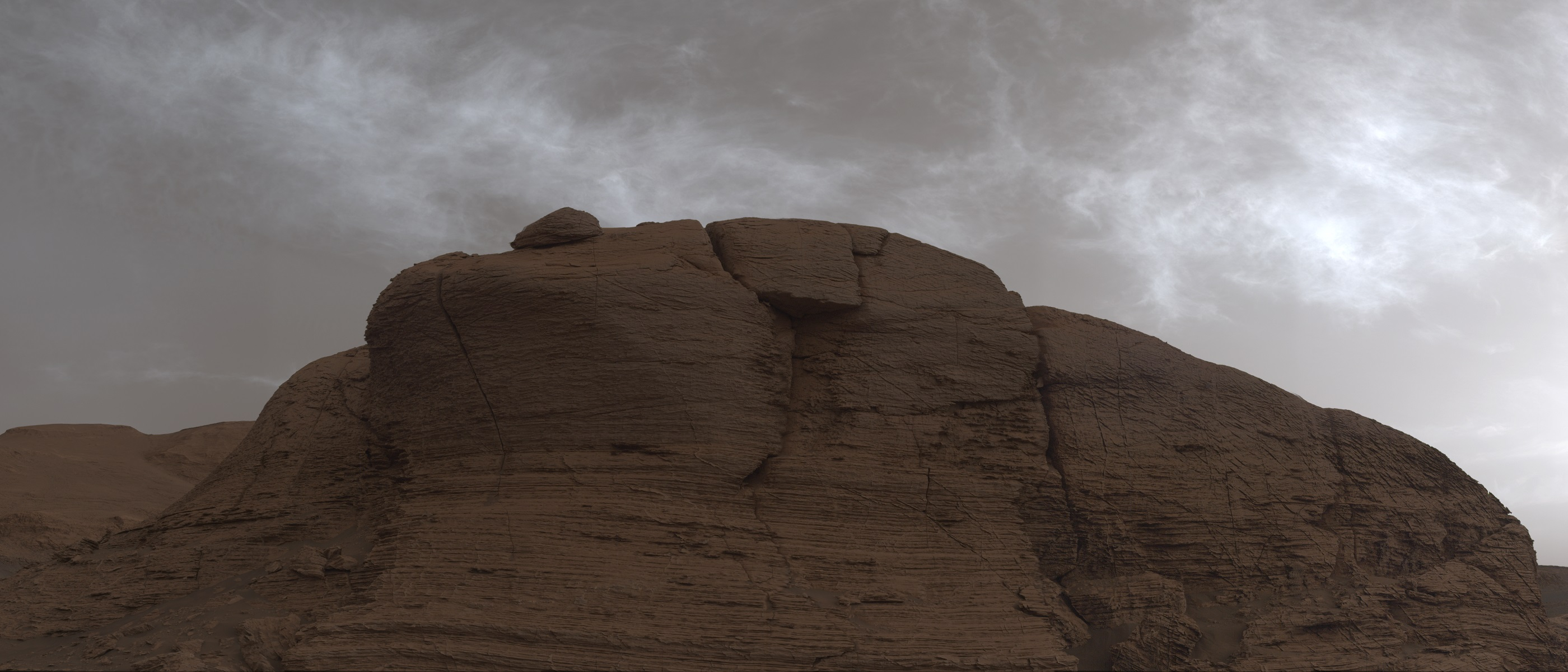 clouds pass above a cliff face on Mars