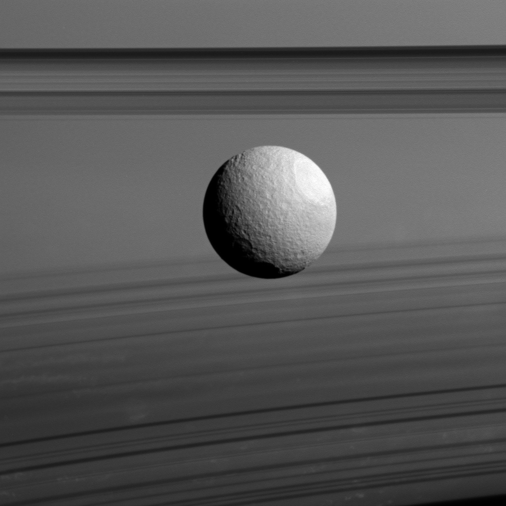 Cassini view of Saturn's moon Tethys against the planet's clouds and rings