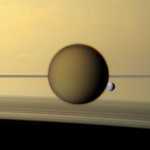The moons Titan and Dione in front of Saturn